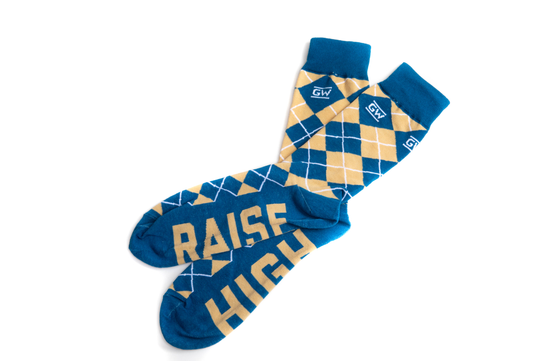 "Blue and yellow argyle socks that say ""Raise High"" on the soles"