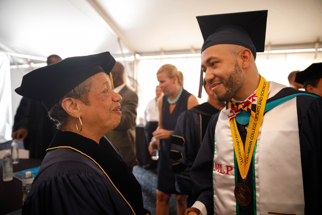 Male graduate talking to Christine Darden, an honorary degree recipient at Commencement