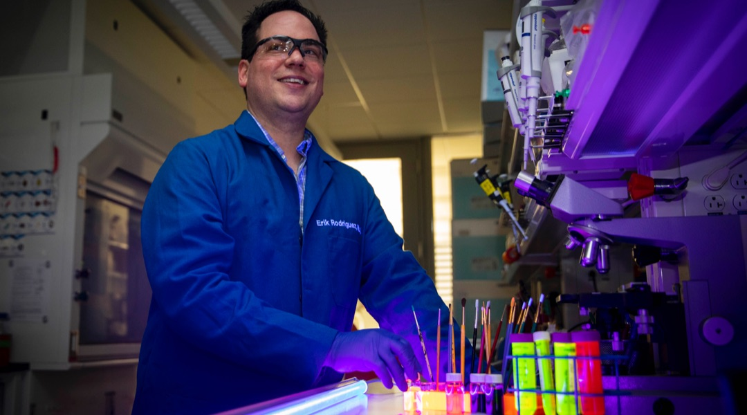 Male researcher in a lab using black lights