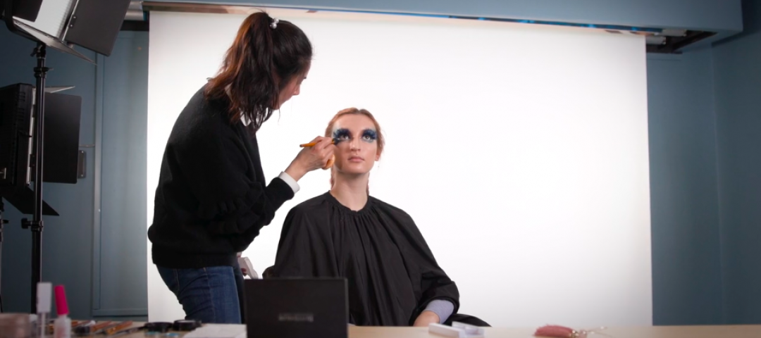 Female makeup artist applying makeup to another female in a studio